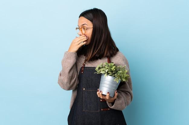 Junge brünette mischrassenfrau, die eine pflanze über isoliertem blauem wandbedeckungsmund hält und zur seite schaut