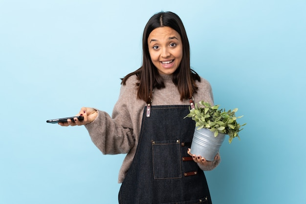 Junge brünette mischrassenfrau, die eine pflanze über lokalisiertem blauem hintergrund hält und ein gespräch mit dem mobiltelefon mit jemandem hält.
