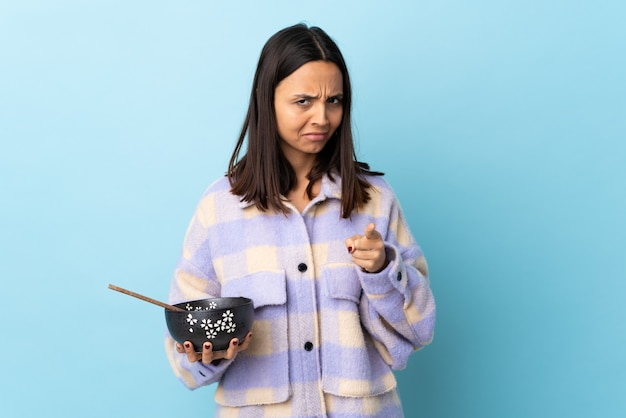 Junge brünette mischrassenfrau, die eine schüssel voll nudeln über isoliertem blau frustriert hält und nach vorne zeigt