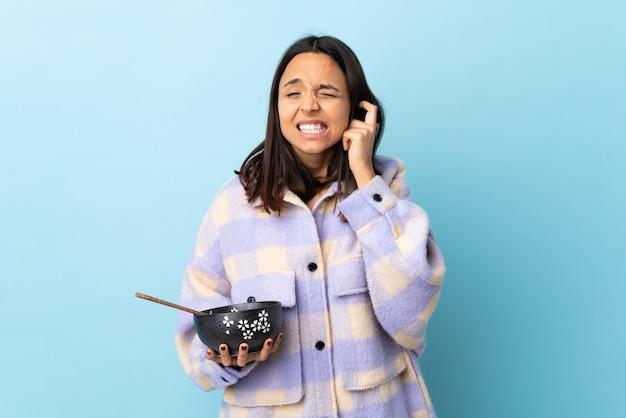 Junge brünette mischrassenfrau, die eine schüssel voll nudeln über isolierter blauer wand hält, frustriert und ohren bedeckt