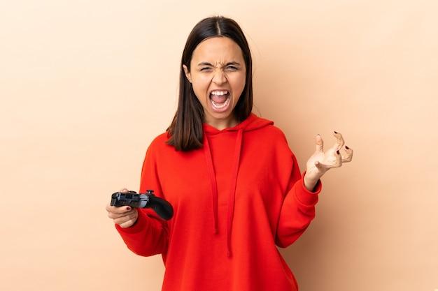 Junge brünette mischrassenfrau, die mit einem videospiel-controller über isolierte wand unglücklich und mit etwas frustriert spielt