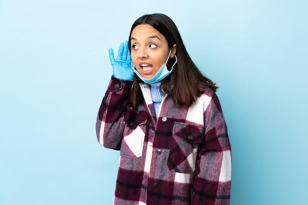 Junge brünette mischrassenfrau, die mit einer maske und handschuhen über blauer wand schützt, die etwas hört, indem man hand auf das ohr legt