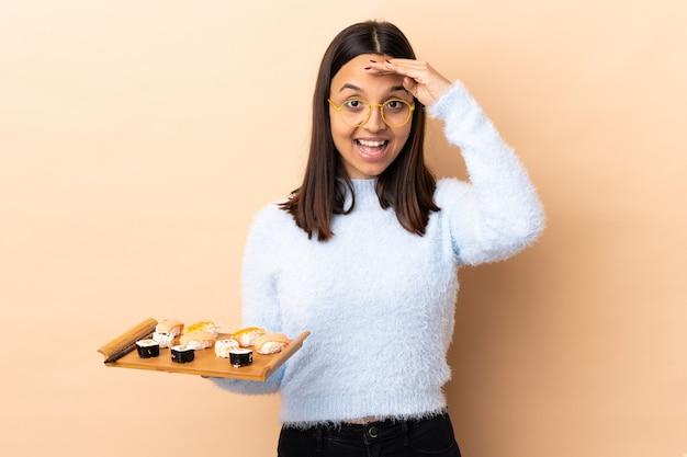 Junge brünette mischrassenfrau, die sushi über isolierter wand hält, die mit hand mit glücklichem ausdruck salutiert