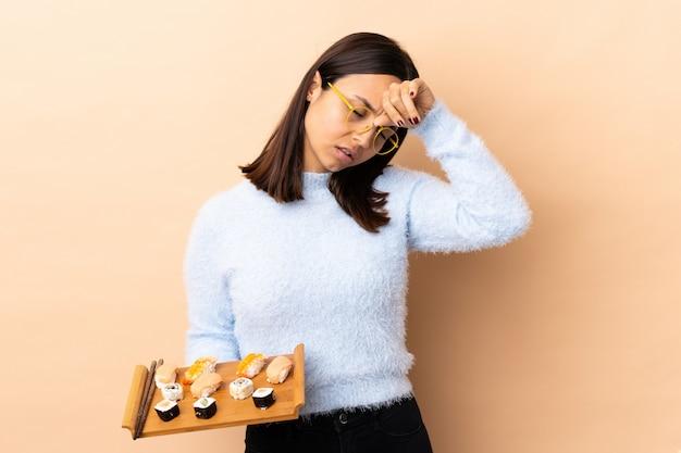Junge brünette mischrassenfrau, die sushi über isolierter wand mit müdem und krankem ausdruck hält