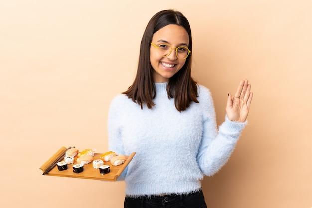 Junge brünette mischrassenfrau, die sushi über wand hält, die mit hand mit glücklichem ausdruck salutiert