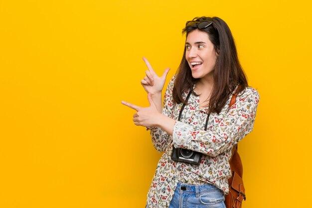 Junge brünette reisende frau, die mit zeigefingern auf einen kopierraum zeigt und aufregung und verlangen ausdrückt.