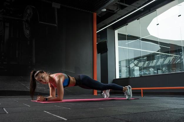 Junge brünette steht in plankenpose auf ellbogen im fitnessstudio