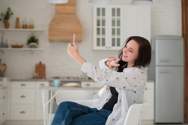 Junge brünette studentin, die mit einem handy in der küche sitzt und ein selfie macht