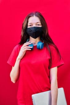 Junge brünette studentin mit maske, die einen laptop und kopfhörer auf rotem hintergrund trägt