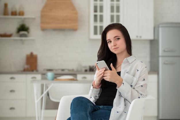 Junge brünette studentin sitzt in der küche mit handy in der hand