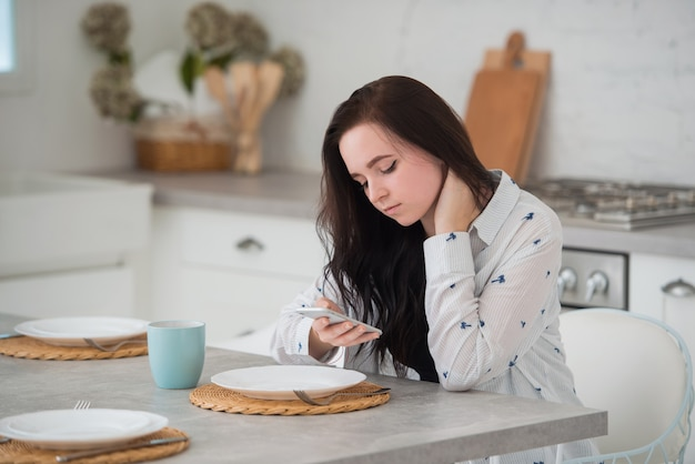 Junge brünette studentin sitzt in der küche mit mobilem smartphone schaut auf den telefonbildschirm