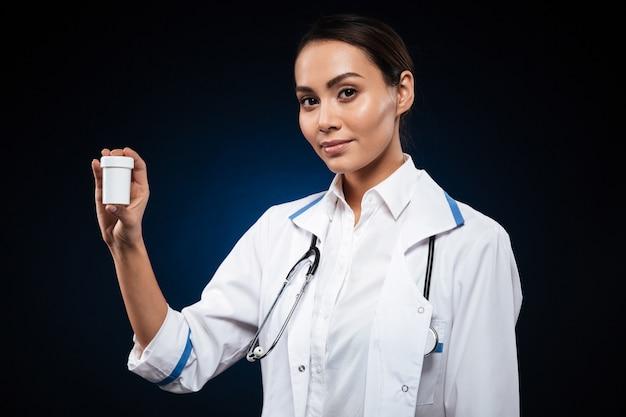 Junge brünette weibliche krankenschwester, die flasche mit pillen lokalisiert zeigt