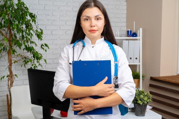 Junge brunetteärztin, die mit klemmbrett in ihrem büro steht