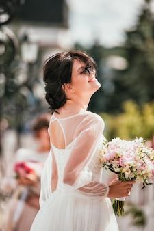 Junge brunettebraut in einem weißen kleid mit blumenstrauß. nahaufnahmeporträt einer frau im freien