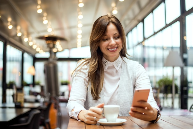 Junge brunettefrau an trinkendem kaffee des cafés und an der anwendung des handys.
