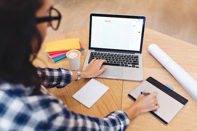 Junge brunettefrau des modernen arbeitsbildes in der schwarzen brille von hinten, die mit laptop auf tisch arbeitet. kreativität, grafikdesign, kluger student, studium, freiberufler.