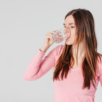 Junge Brunettefrau, die das reine Wasser lokalisiert auf grauem Hintergrund trinkt