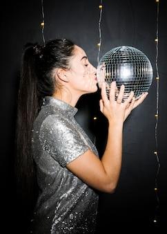 Junge brunettefrau, die discokugel küsst