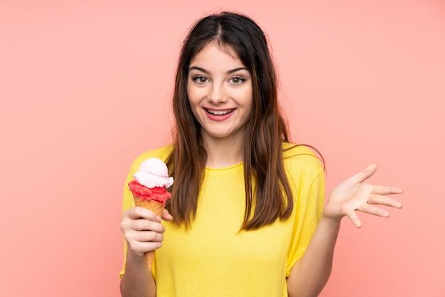 Junge brunettefrau, die eine kornetteiscreme über rosa wand mit entsetztem gesichtsausdruck hält