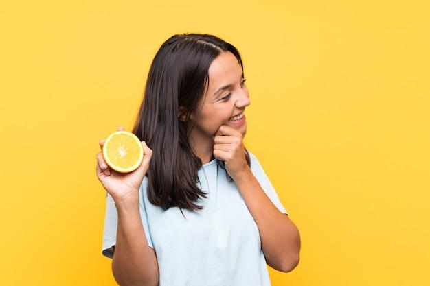 Junge brunettefrau, die eine orange denkt eine idee und schaut seite hält