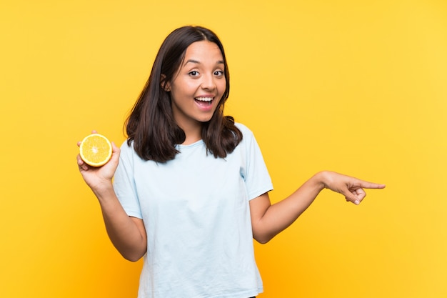 Junge brunettefrau, die eine orange überrascht hält und finger auf die seite zeigt