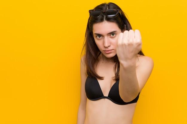 Junge brunettefrau, die einen bikini auf der gelben darstellenden faust zur kamera, aggressiver gesichtsausdruck trägt.