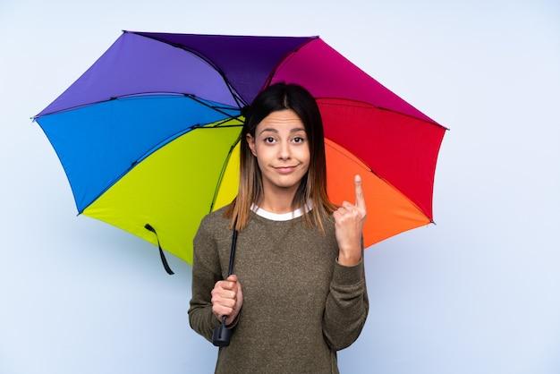 Junge brunettefrau, die einen regenschirm über der blauen wand zeigt mit dem zeigefinger eine großartige idee hält