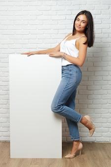 Junge brunettefrau, die großes leeres weißes brett mit kopienraum hält