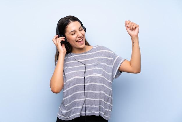 Junge brunettefrau, die musik mit kopfhörern hört