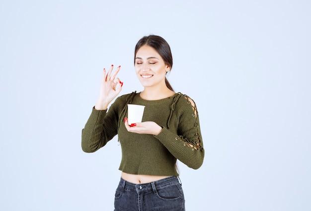 Junge brunettefrau, die okayzeichen für tee auf weißem hintergrund gibt.