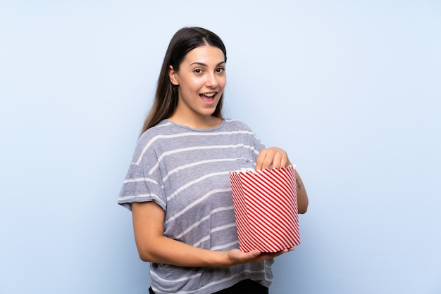 Junge brunettefrau, die popcorn isst