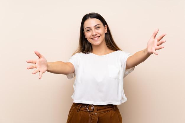 Junge brunettefrau, die sich darstellt und einlädt, mit der hand zu kommen