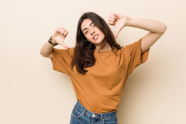 Junge brunettefrau, die unten daumen zeigt und abneigung ausdrückt.