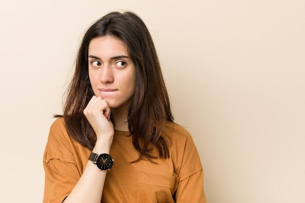 Junge brunettefrau gegen einen beige verwirrten hintergrund, glaubt zweifelhaft und unsicher.