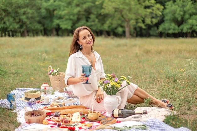 Junge brunettefrau genießen picknick im freien auf grünem rasen.