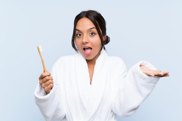 Junge brunettefrau im bademantel, der ihre zähne mit entsetztem gesichtsausdruck putzt