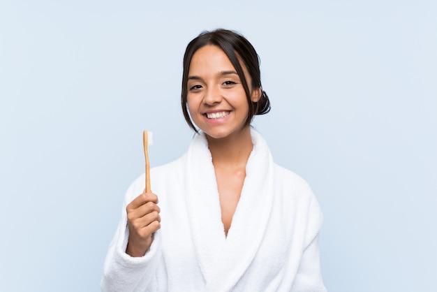 Junge brunettefrau im bademantel, der ihre zähne über dem lokalisierten blau viel lächelt putzt