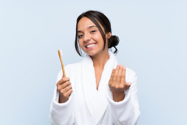 Junge brunettefrau im bademantel, der ihre zähne über der lokalisierten blauen wand einlädt, mit der hand zu kommen. schön, dass sie gekommen sind