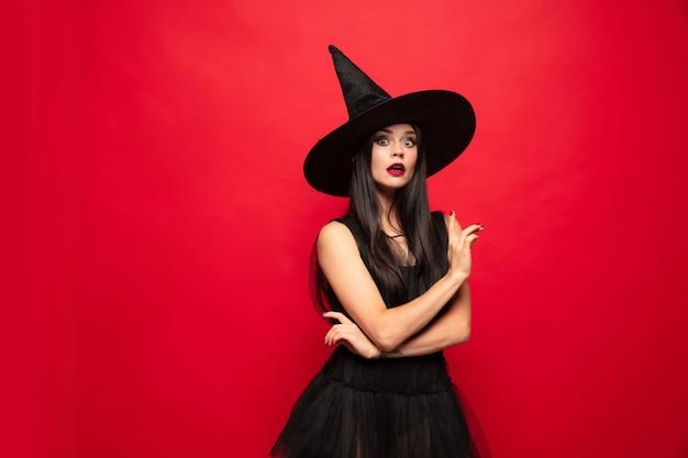Junge brunettefrau im schwarzen hut und im kostüm auf rotem hintergrund. attraktives kaukasisches weibliches modell. halloween, schwarzer freitag, cyber-montag, verkauf, herbstkonzept. exemplar. nach oben zeigend.