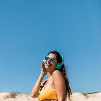 Junge brunettefrau in den kopfhörern