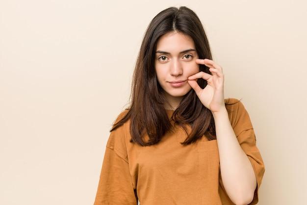 Junge brunettefrau mit den fingern auf den lippen, die ein geheimnis halten.