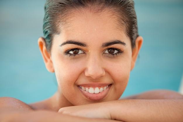 Junge brunettefrau nass im pool