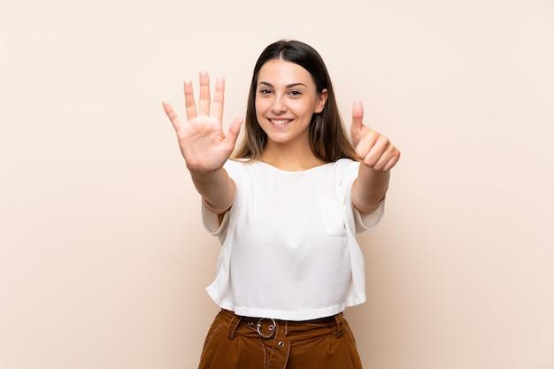 Junge brunettefrau trennte das zählen von sechs mit den fingern