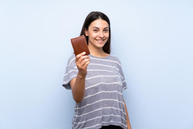 Junge brunettefrau über dem lokalisierten blauen hintergrund, der eine geldbörse hält