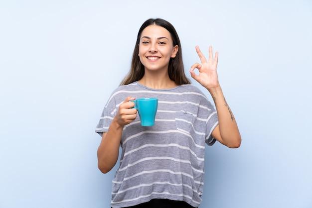 Junge brunettefrau über dem lokalisierten blauen hintergrund, der heißen tasse kaffee hält