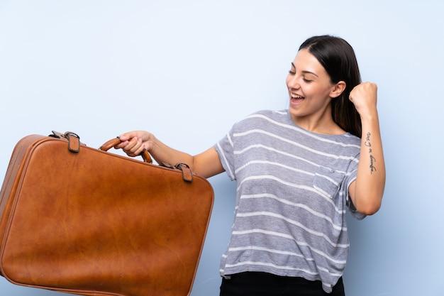 Junge brunettefrau über der lokalisierten blauen wand, die einen weinleseaktenkoffer hält