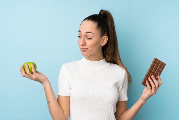 Junge brunettefrau über der lokalisierten blauen wand, die zweifel beim nehmen einer schokoladentafel in einer hand und eines apfels in der anderen hat