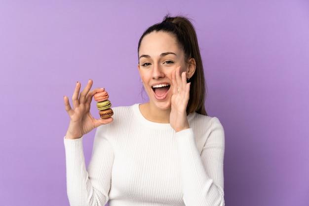 Junge brunettefrau über der lokalisierten purpurroten wand, die bunte französische macarons und das schreien hält
