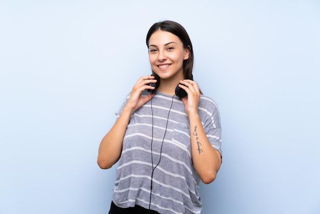 Junge brunettefrau über lokalisiertem blauem hintergrund hörend musik mit kopfhörern