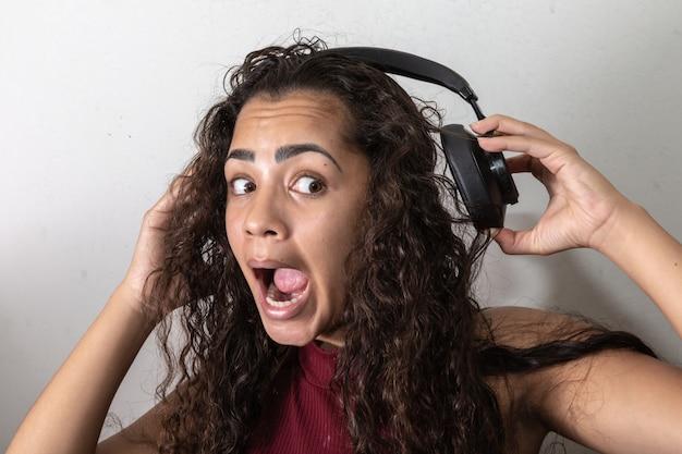 Junge brunettefrauenüberraschung mit hohem volumen kopfhörern